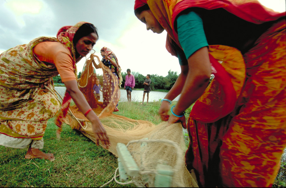 Rural women prepare nets for fishing in Hamidpur, Bangladesh. An IFAD-initiated microfinance scheme has enabled hundreds of women in the region to start their own fish-production enterprises. ©IFAD/Alexandra Boulat