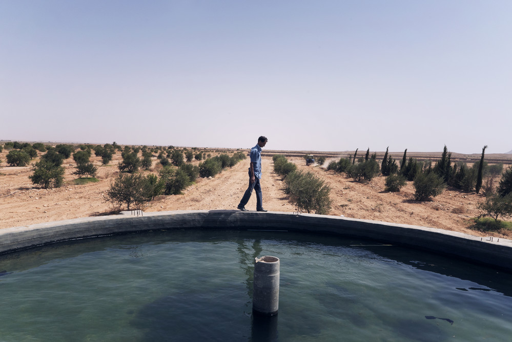 Aoun walks on the side of a water tank used to irrigate cultivated fields. © IFAD/Alfredo D'Amato/Panos