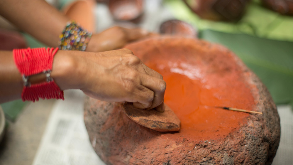 Qichua Indigenous artisan extracts the color from natural rocks. IFAD/Carla Francescutti